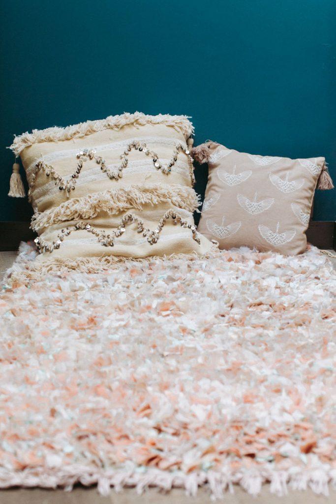 Tapis ADEL :  tapis boucharouite réalisé en tissage artisanal et ancestral à partir des tissus Lorafolk aux tons pastels et irisés - 380€ -  Coussin ALI : réalisé à partir de tapis anciens Handira, tissé à la main - 80€ -  Coussin RAJ : canevas brodé de fil et de perles selon le motif emblématique du Bazar par Lorafolk - 65€ | ©Laurence Revol