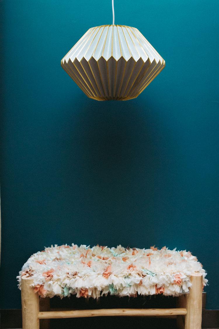 Suspension ARUN : 70€ - Suspension en origami en papier vert d'eau et arrêtes dorées à chaud. Banquette INES : 170€ - Banquette en bois de citronnier sculpté à la main et assise en tissage artisanal boucharouite réalisé à partir de tissus Lorafolk. | ©Laurence Revol